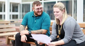 A man and woman, his compensated work therapy program vocational rehabilitation specialist, sit together on an outdoor bench