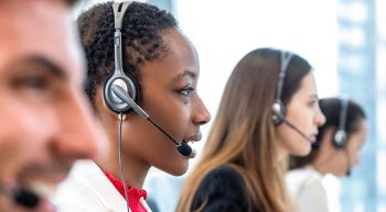 A profile photo of four call center employees talking into headsets