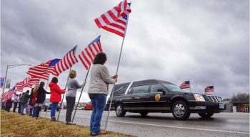 People hold flags as a funeral hearse passes