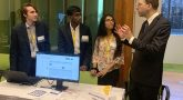 """IMAGE: Dr. Gil Alterovitz, Director, National Artificial Intelligence Institute, Department of Veterans Affairs, (right) with members of the Girls Computing League discuss the Clinical Trial Selector project at last week's """"demo day"""" at the U.S. Census Bureau, Department of Commerce."""