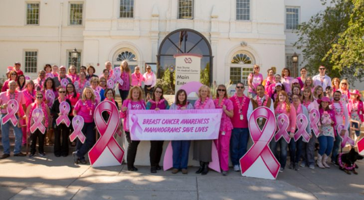 Northern Arizona VA Health Care System staff show their pink in front of the building for breast cancer awareness