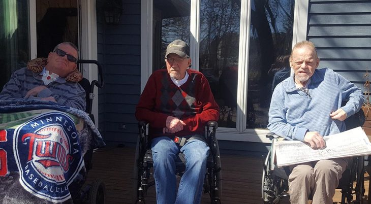 Three men sit outside a medical foster home in wheelchairs