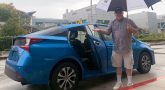 A man who is in the vocational rehab program with an umbrella motions you into his car