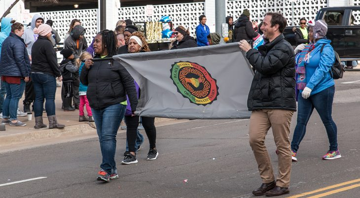 Two people carry a banner in a parade