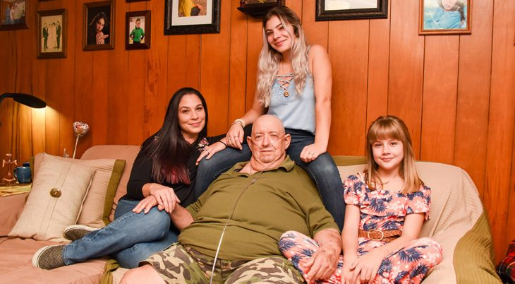 Man sits on a sofa, surrounded by three women