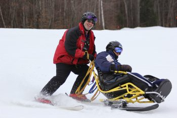 A VA volunteer assists a Veteran with skiing at the New England Winter Sports Clinic for Veterans with Disabilities.