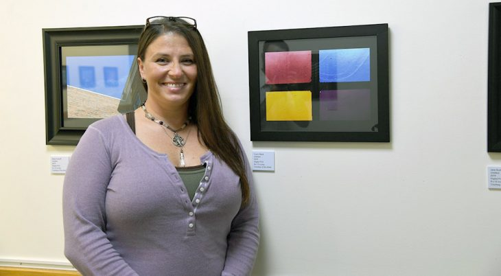 A woman stands in front of her art in a gallery