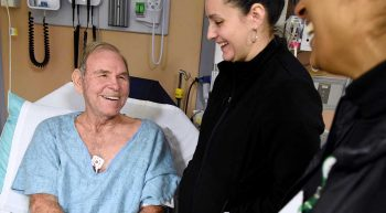 Smiling man in hospital bed talking to a nurse
