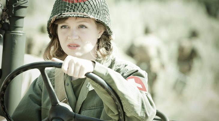 Female military medic driving vehicle in field