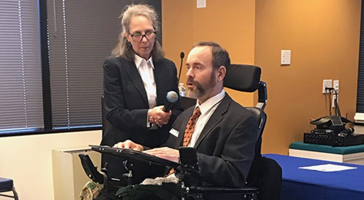 Woman holds microphone for man in wheelchair who has MS