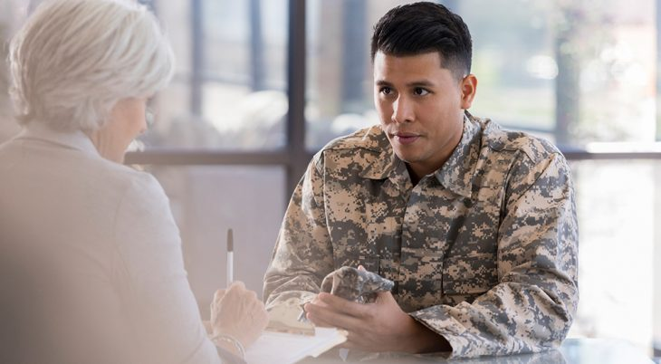Young army soldier listens as a female therapist gives him advice regarding low blood sugar. The therapist is taking notes in the patient's chart.