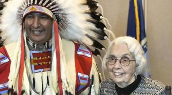 A native American chief in full headdress and a senior woman