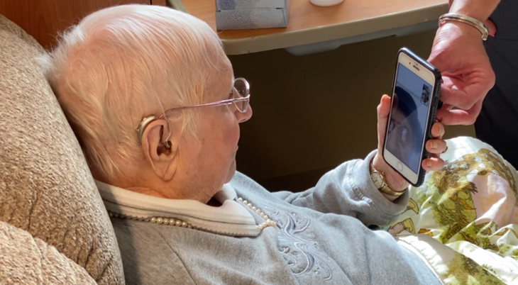 An elderly lady speaks with her sister on her smart phone