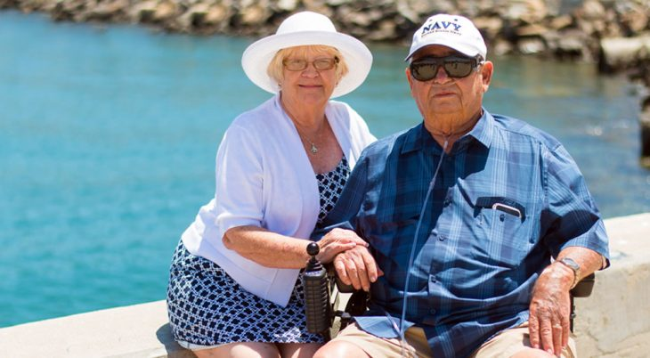 And elderly man wearing a Navy Veteran cap and his caregiver wife sit by the water