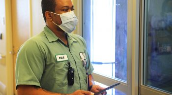A housekeeper wearing a mask holds a phone