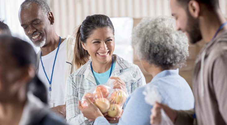 Cheerful mid adult female food bank volunteer receives a bag of fresh apples from a mature woman.