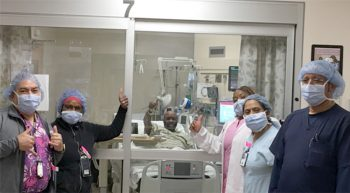 A coronavirus patient in hospital bed joins health care team for a thumbs up