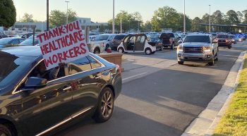 A car with a sign saying Thank You leads a procession of vehicles full of people showing their appreciation