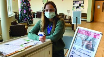 Young woman who is a student volunteer, in mask holds thermometer