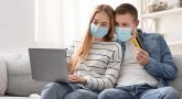 Young couple wearing masks working on laptop use a credit card to pay a debt