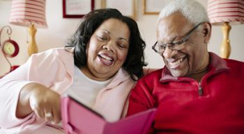 Geriatric man and woman reading and smiling