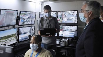 Several people in a control room with monitors