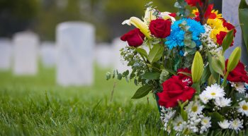 white grave markers and flowers at a national cemetery