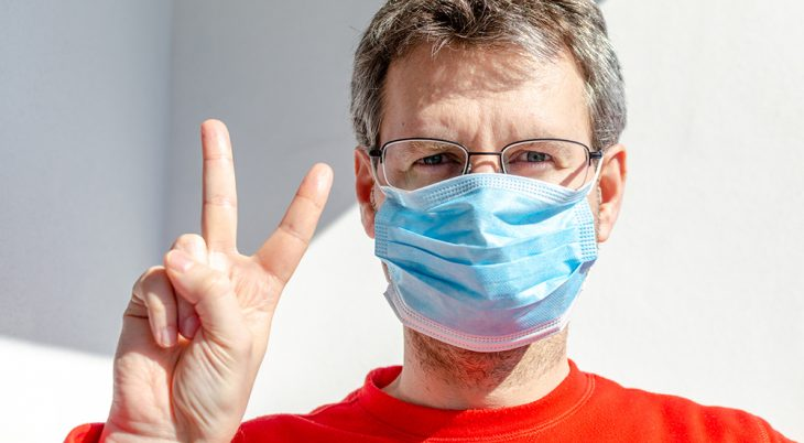 A portrait close up of a man in a protective mask and eyeglasses against a white wall background with sunshine