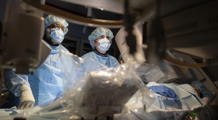 Two doctors watching monitors during surgery