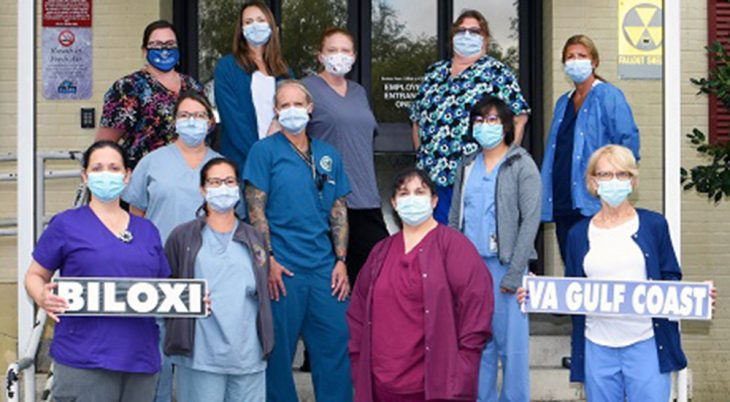 Twelve nurses wearing masks at hospital entrance and holding signs that say Biloxi and VA Gulf Coast