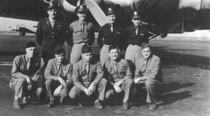 Nine men in uniform in front of airplane