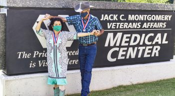 Man and woman dancing in front of VA medical center sign