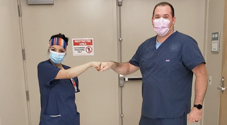 Two nurses in masks fist bump