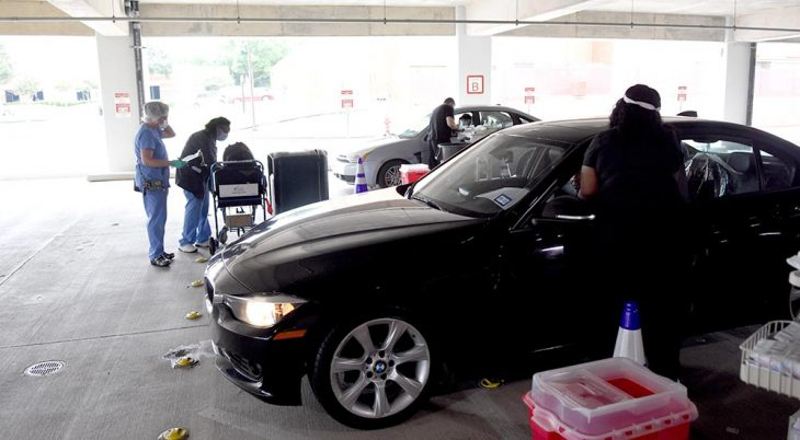 Two cars lined up in an open garage