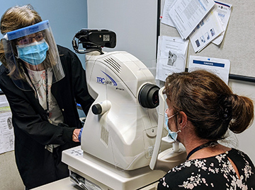 Clinician scanning a patient's eyes