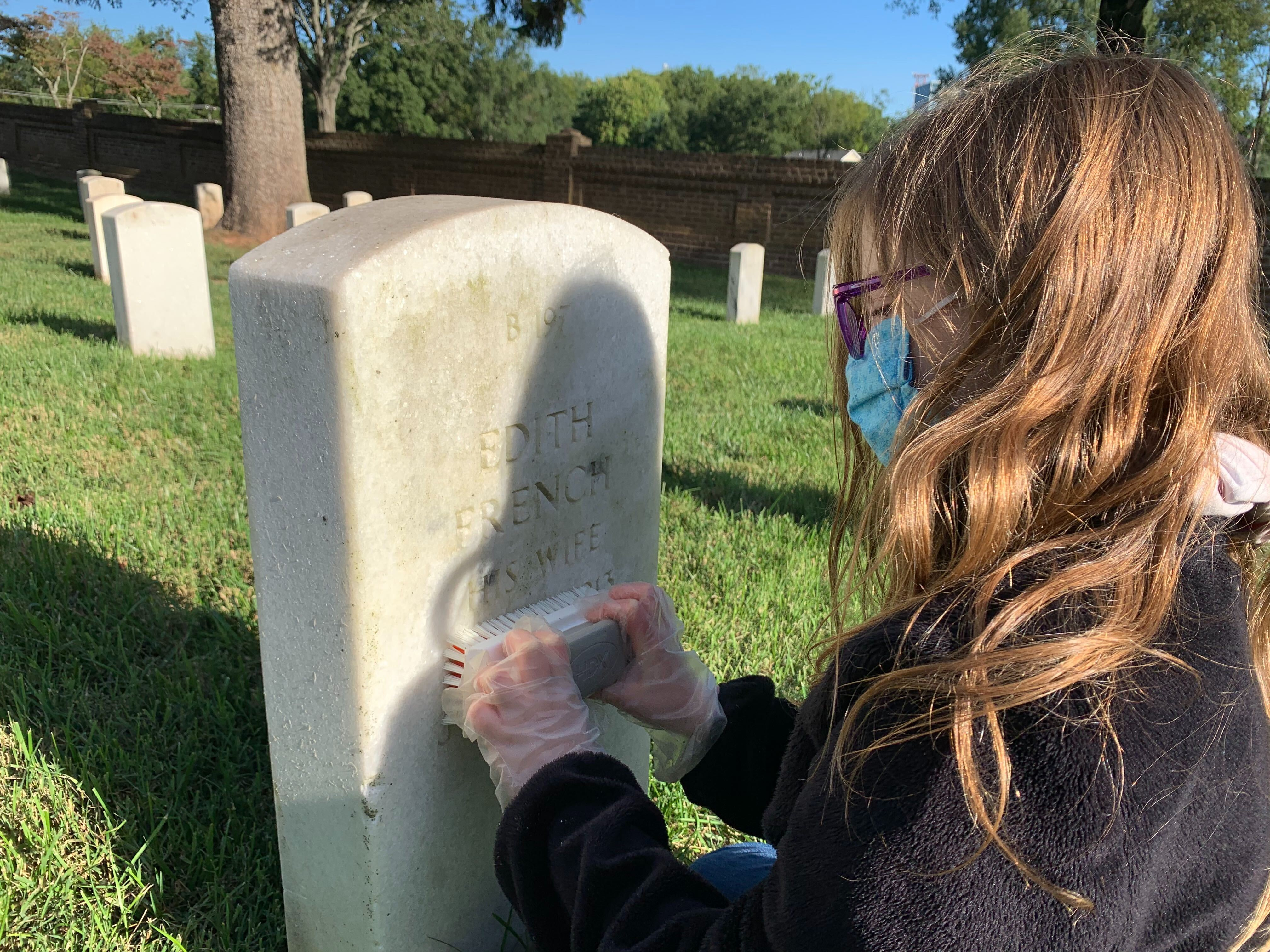 Elleana Bowler cleans a headstone Sept. 19 at Culpeper National Cemetery in Virginia.