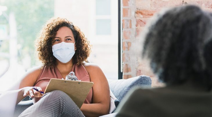 A caring mid adult female therapist wears a protective face mask a she listens to an unrecognizable female client during a therapy session