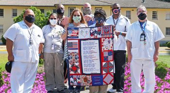 Large group of VA employees wearing mask and presenting quilt