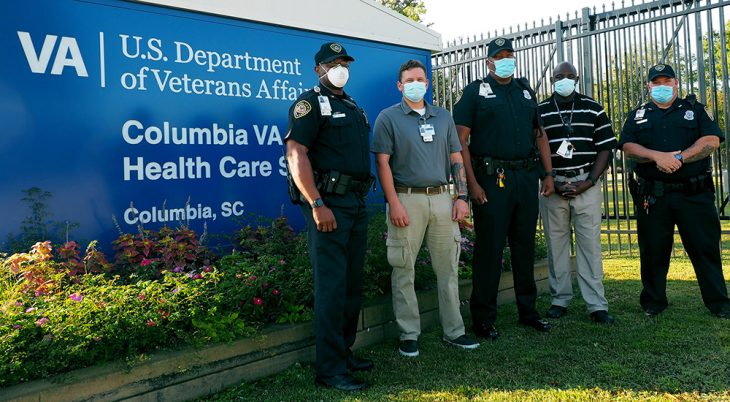 Five police officers in front of hospital sign