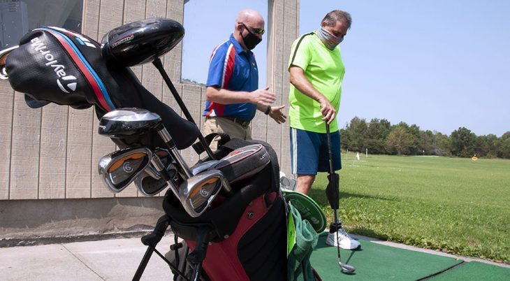 Man explaining golf stance to amputee Veteran