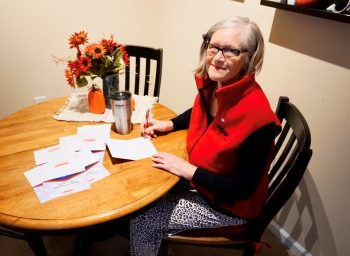 women volunteer writes thank you notes