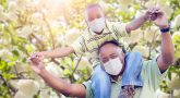 African American Father And Son Playing Outdoors Wearing Medical Face Mask.