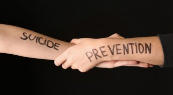 Female hands with text SUICIDE PREVENTION on dark background