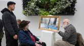 man shows his painting to visitors