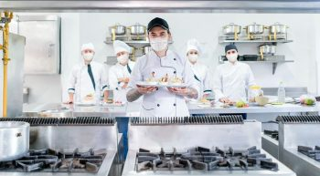 Cook with a catering team wearing facemasks in a commercial kitchen while presenting a plate and looking at the camera – pandemic lifestyle concepts
