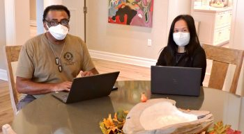 Man and woman wearing masks working on laptops
