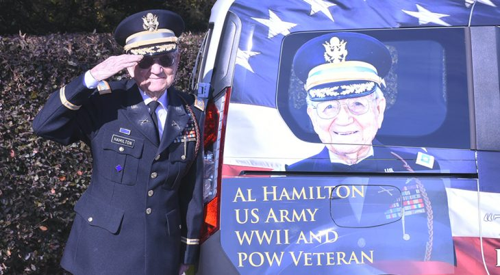 Elderly Army Veteran salutes next to a van with his image painted on it