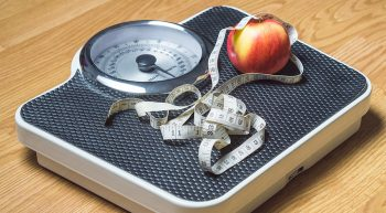 Apple and measuring tape on a scale
