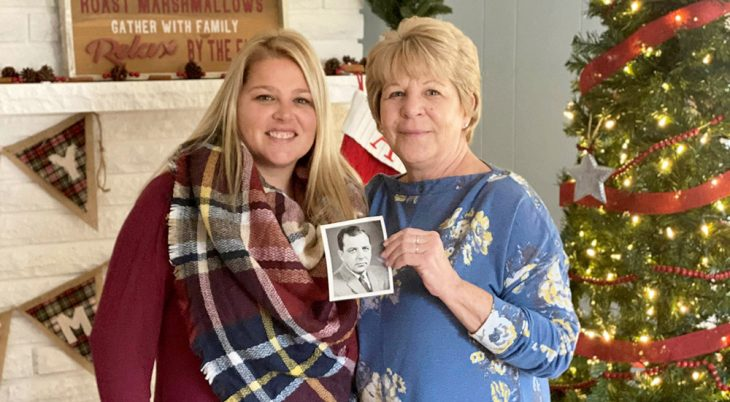 Pam Lajoie stands with her daughter, Shannon Cochran while holding a photograph of her father, Art Middleton. Both carry on their father's legacy of caring for Veterans as VA staff members in Battle Creek.