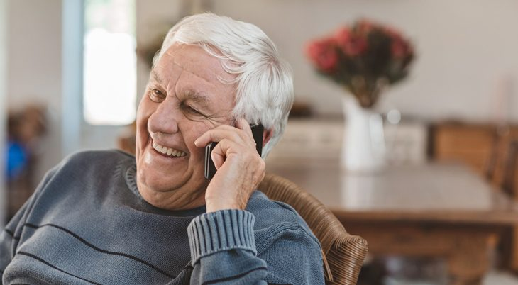 Laughing senior man talking on a cellphone while relaxing in a chair in his living room at home